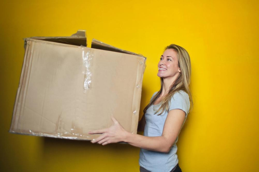 woman-in-grey-shirt-holding-brown-cardboard-box-761999.jpg